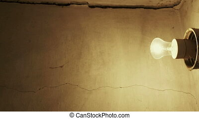 Light bulb glowing on grunge concrete wall in old house
