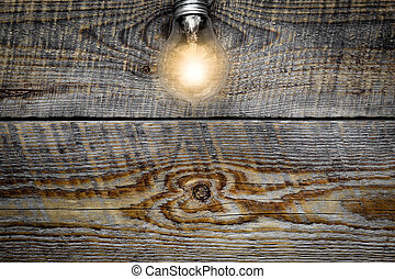 Light bulb glowing on wooden background