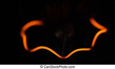 Light bulb helix on black background, macro