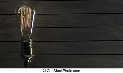 light bulb illuminates on wooden background.