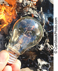 Light bulb in hand on a background of fire, texture