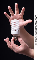 Light bulb in hand on a black background