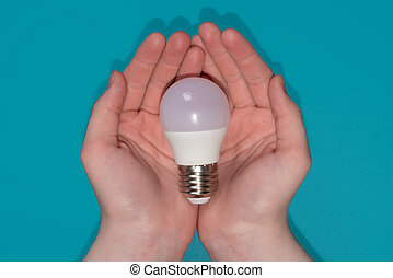 light bulb in hands on the blue background.