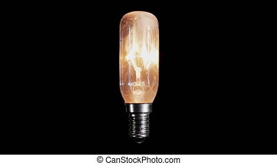 Light bulb lamp flickers and burns out with flame over black background