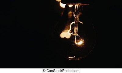 Light bulb lit brightly against a black background