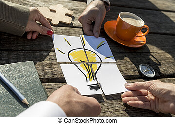 Light bulb on a rustic wooden table outdoors in the sunlight