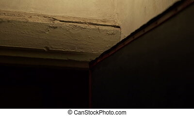 Light bulb on cracked concrete wall in old house tilt up closeup