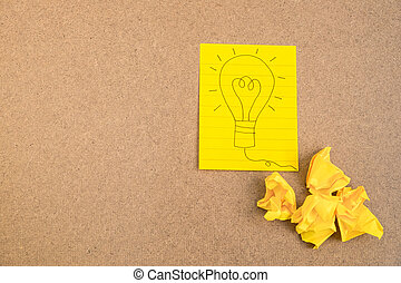 Light bulb on yellow paper with crumpled paper