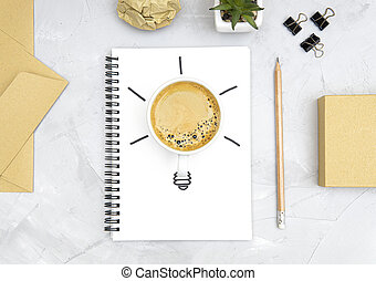 Light bulb symbol made of a fresh cup of coffee and a sketch on a spiral notebook. Office workplace flat lay. Refreshment and productivity concept. Boosting brain function with caffeine.