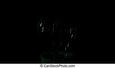 Light bulb turning on on black background in slow motion