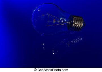 Light bulb with burning filament lay on blue shiny surface with reflection