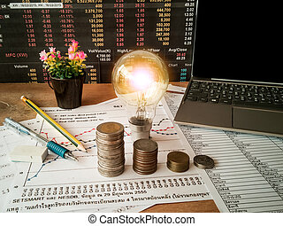 Light bulbs are placed on business accounting documents and the concept of energy saving and financial accounting of the company.