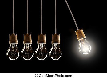 Light bulbs in row with single one in motion and shinning, isolated on black background