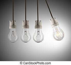 Light bulbs in row with single one shinning - Light bulbs in...