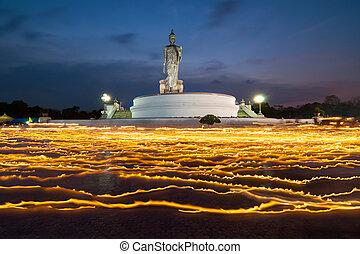 light candle with buddha image at twilight