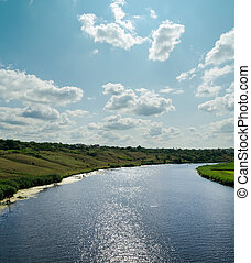 light clouds in blue sky over river with reflections