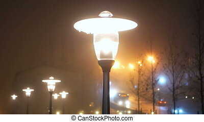 Light foggy night lantern - Ground light in foggy night with...