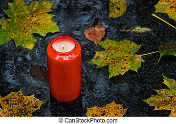 light grave on all saints day in the fall with leaves - a...