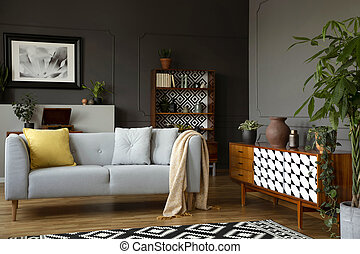 Light grey sofa with blanket and pillows standing in real...