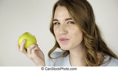 Light haired woman biting a green apple and looking at camera