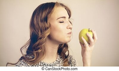 Light haired woman biting a green apple and looking at camera toned