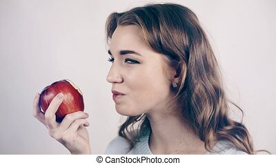 Light haired woman biting a red apple and looking at camera