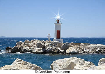 A man standing next to a small light house on a windy day