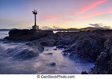 Beautiful twilight seascape with lighthouse on the island