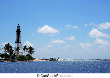 Black and white light house with clear blue sea.