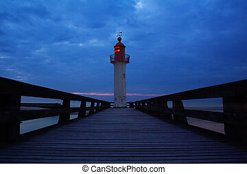 Light house in Normandy, France, at sunset with dark blue ...