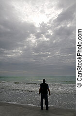 Light in the Dark - A man standing on the beach looking at a...