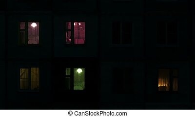 Light in the windows of high-density apartment block at night