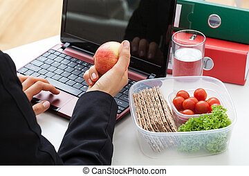 Light meal at work - Business woman eating light meal at...