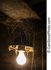 Light of old lamp in a creepy room with cobwebs