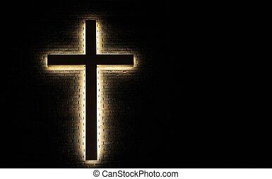 Illuminated cross on a brick wall.