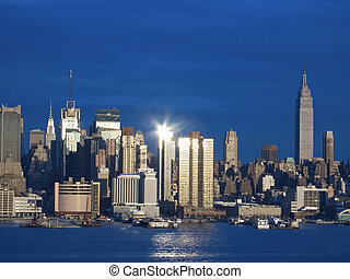 This is a shot of the sun reflecting off of the New York City skyline in the late afternoon.