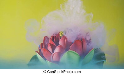 Light pink and white colorful clouds of ink or paint swirling and covering red flower underwater