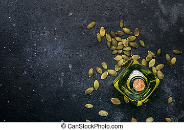 Light pumpkin seeds oil in glass jar on gray kitchen table background, top view