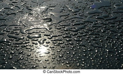Light rain dripping on a shiny smooth floor with small formed puddles, close view. Reflection of the sun in drops of water. Sunny and rainy weather. Water pours onto the surface of graphite color.