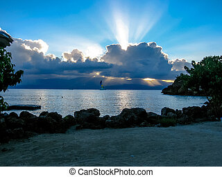 Tropical landscape of Guadalupe in the French Caribbean in the summer at sunset with low clouds in the sky over the sea.