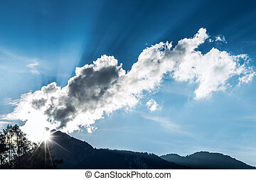 light rays through clouds over mountain top at blue sky