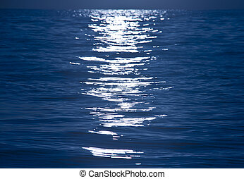 Light reflection on blue rippling water