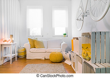 White interior with double linen sofa, yellow accessories and handmade shelf