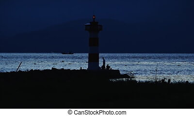 Light Shining in the North Head Lighthouse on the Washington Coast at Sunset. Fishermen with fishing rods catch fish from the ocean.