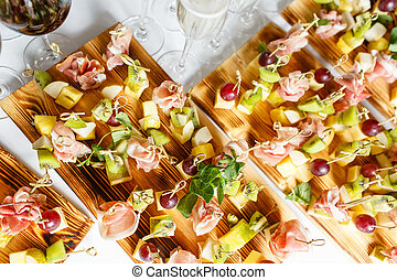 Light snacks in a plate on a buffet table. Assorted mini ...