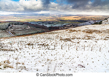 Light snow over fields, hills and trees. Looking down on Vale of Neath, South Wales, United Kingdom.