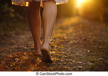 Light steps - Young female legs walking towards the sunset ...
