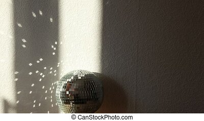 Light strips moves by a mirror ball, patches of light on a wall. Time lapse.