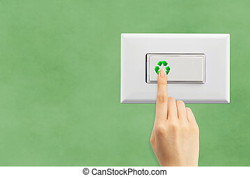 Light switch and hand on a green wall background, ecology concept
