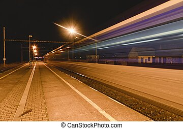 Light trail of the express train in the railway station at the night. Railway platform a the night